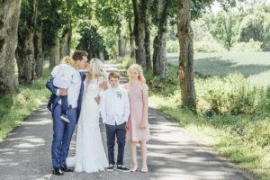 Bröllopspar som pussas. Barnen är med på bilden.