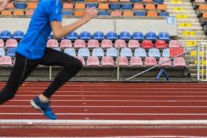Ben som springer på en arena.