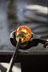 Glasblåsning - bild på rött varm glas som skålas i en träform