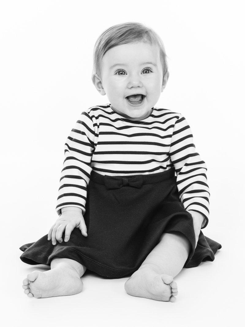 Bild på ett glatt barn som sitter.
