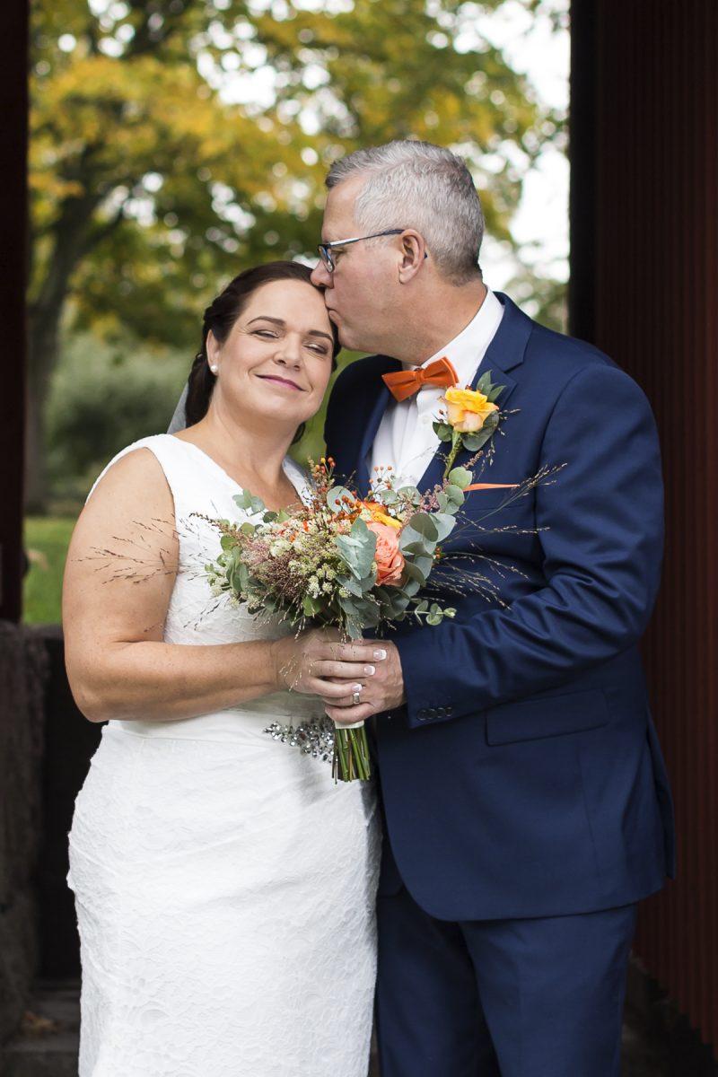 Bild på ett bröllopspar. Hon får en puss i pannan.