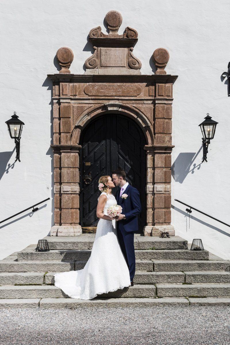 Bröllopspar som pussar på en trappa.