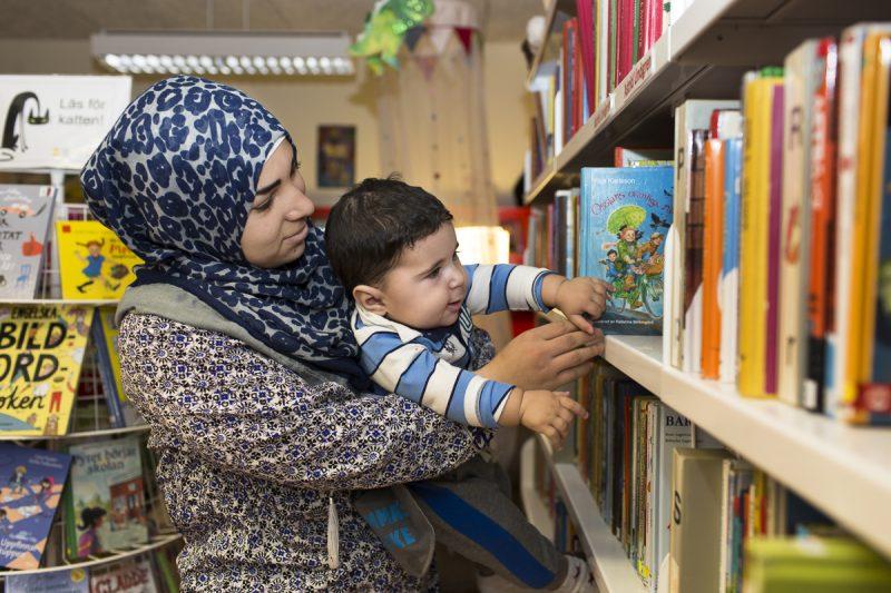 En mamma med sjal som tittar på böcker i bokhyllan.