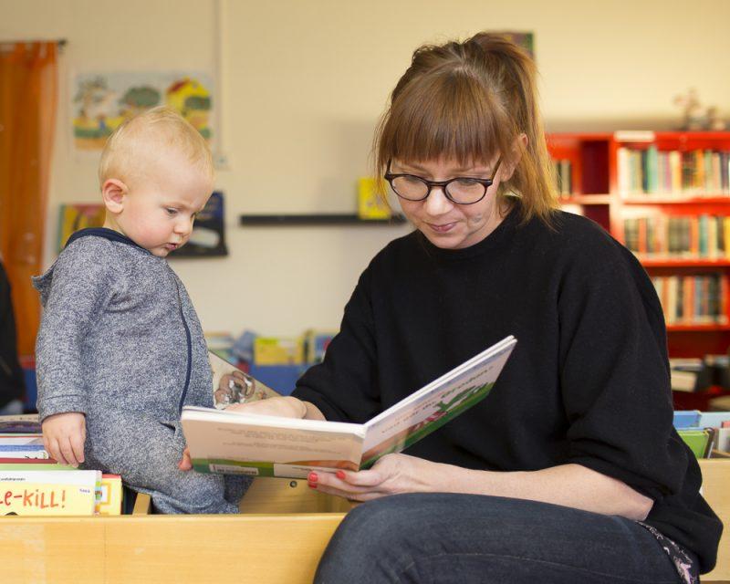 Mamma som läser en bok för sin son.