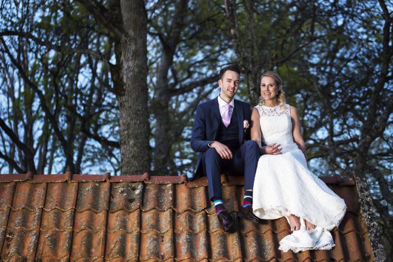 Bild på ett bröllopspar som sitter på en takås.