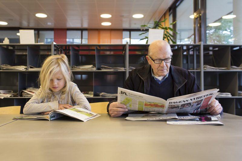 En äldre man och en yngre tjej sitter på bibblan och läser.