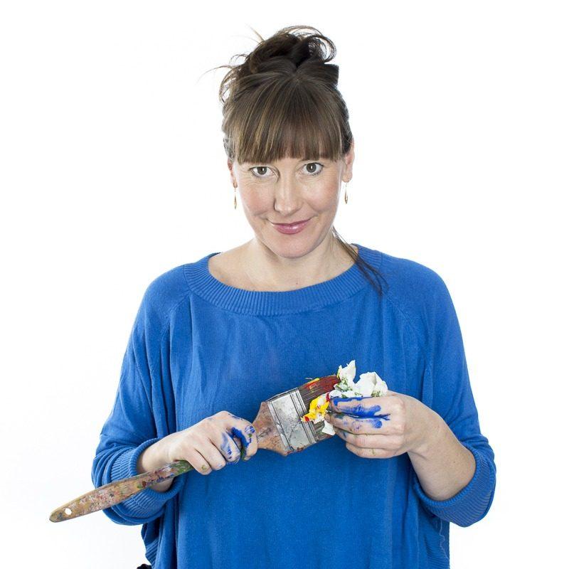 Emilia Linderholm - en konstnär med blå tröja och en färgpensel.