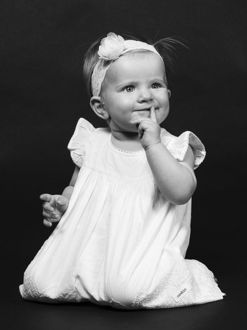 En ettåring med finurligt leende och vit klänning.
