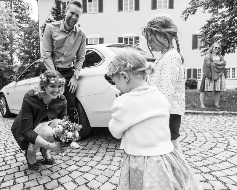 Bröllopsbild med bruden som sitter på huk och pratar med barn.