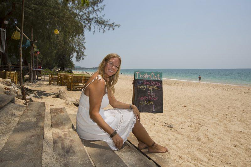 Kvinna sitter på en trappa på stranden i Thailand.
