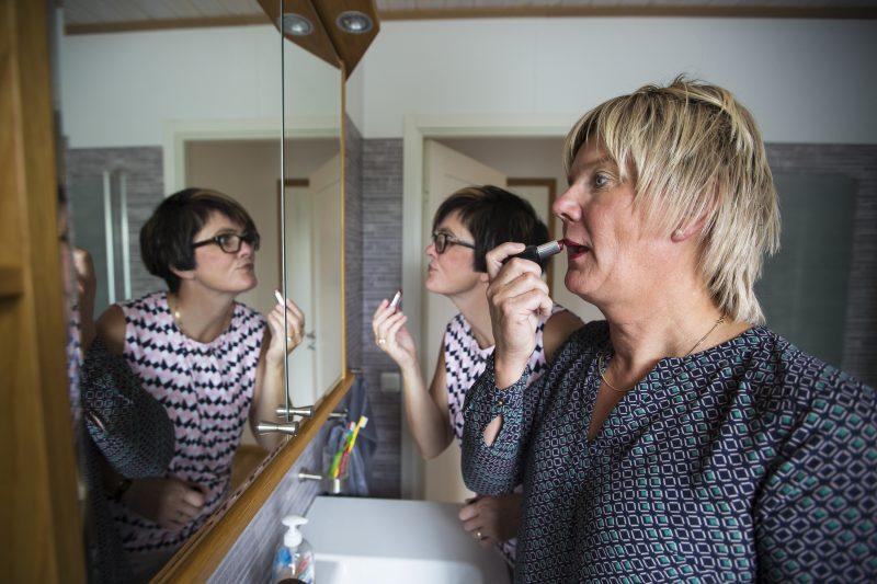 Tillsammans målar det läpparna framför spegel, han har blivit fru till sin fru.
